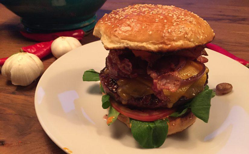 """""""Hot-Mojo-Burger"""" mit frischen Buns, argentinischem Angus-Beef, Feldsalat, Tomate, Cheddar, krossem Bacon, glasierten Zwiebeln, Bacon-Jam und Mojo-Rojo"""